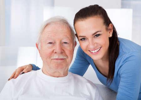 Portret van jonge vrouwelijke verzorger met senior man in verpleeghuis