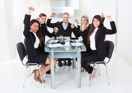 Portrait of successful business team with arms raised sitting at desk at office photo