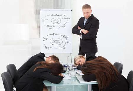 オフィスでのプレゼンテーション中に眠っている疲れている同僚を見て怒っている実業家 写真素材