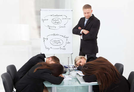 boardroom: Angry businessman looking at tired colleagues sleeping during presentation in office