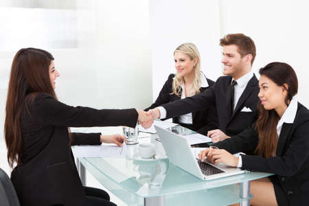 law suit: Business colleagues shaking hands at desk in office Stock Photo