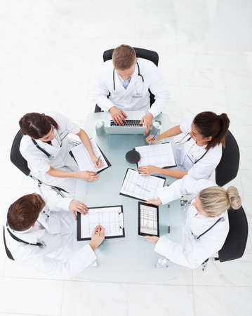 High angle view of doctors analyzing medical reports at desk in clinic