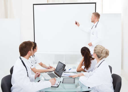 Doctor giving presentation to colleagues in meeting at hospital