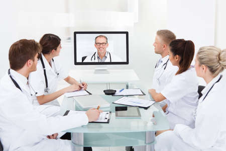 Webinar: Team of doctors attending video conference at desk in hospital Stock Photo