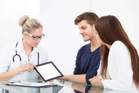 Female doctor showing medical report to couple on digital tablet at clinic photo