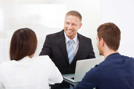 Smiling financial advisor discussing with young couple at office desk