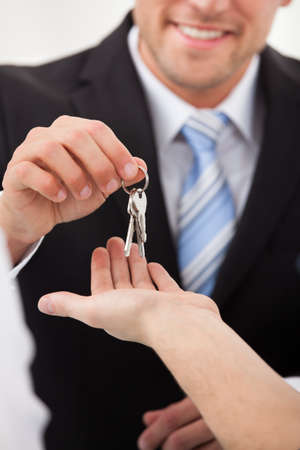 house keys: Cropped image of estate agent giving house keys to man in office