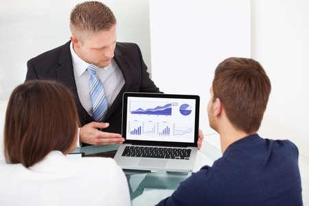 사무실 책상에서 랩톱에 투자 계획을 설명하는 재무 고문