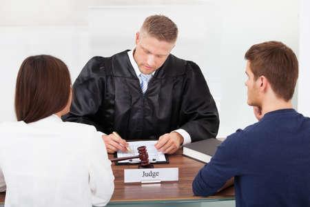裁判官の裁判所でデスクを書くのカップルの背面図