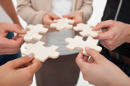 Bebouwd beeld van ondernemers bij puzzelstukjes in kantoor Stockfoto