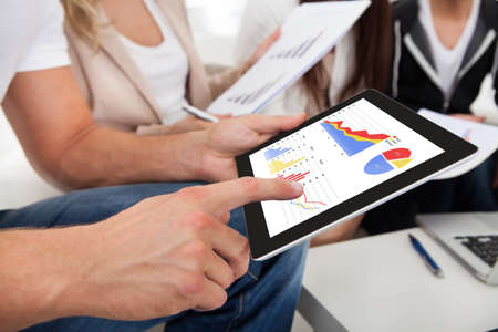 Cropped image of businesswoman touching digital tablet in office photo