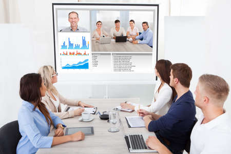 Business team attending video conference at desk in office