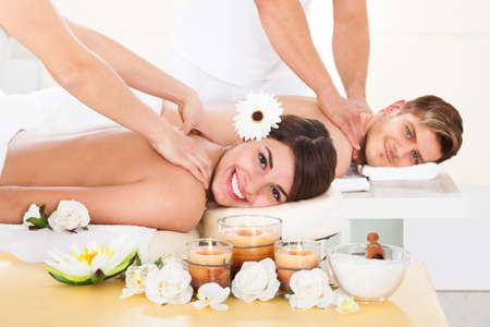 massage table: Portrait of smiling young couple receiving massage at spa Stock Photo