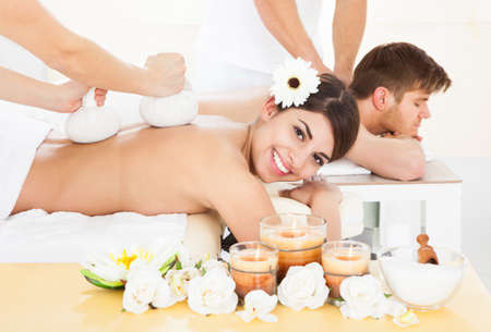 compress: Portrait of happy woman receiving massage with herbal compress stamps on back at spa Stock Photo