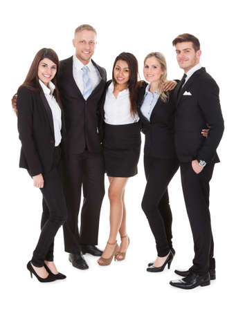 arms around: Full length portrait of welldressed businesspeople standing together against white background