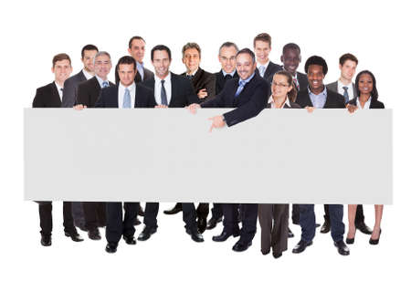 Multiethnic businesspeople holding blank billboard against white background photo