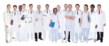 Grote groep artsen vertrouwen staande tegen een witte achtergrond