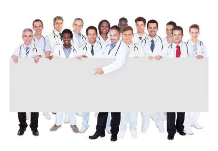 grupo de médicos: Grupo grande de médicos confía en pie contra el fondo blanco