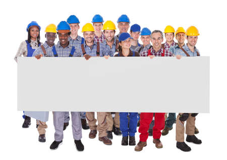 Portrait of multiethnic manual workers holding blank banner against white background photo