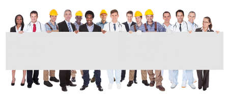 Full length portrait of smiling people with various occupations holding blank billboard over white background photo