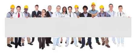 tradesmen: Full length portrait of smiling people with various occupations holding blank billboard over white background Stock Photo