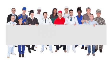 blank banner: Full length portrait of smiling people with various occupations holding blank billboard over white background Stock Photo