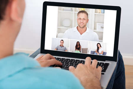 video conference: Man having video conference with friends on laptop at home Stock Photo