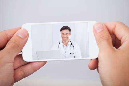Man having video chat with doctor on smartphone photo