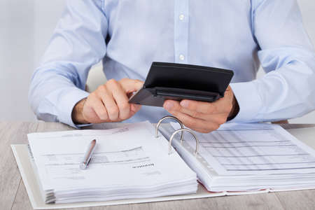 account executives: Midsection of businessman calculating financial expenses at desk