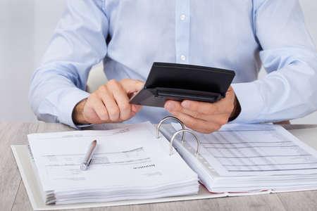 auditor�a: Secci�n media de hombre de negocios c�lculo de los gastos financieros en el escritorio