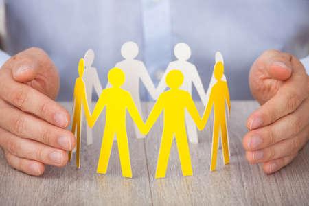 personas ayudando: Detalle de las manos que protegen el equipo de personas de papel sobre el escritorio