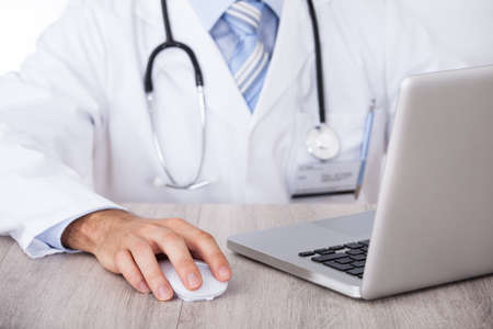 Midsection of male doctor using laptop and mouse at desk in clinic photo
