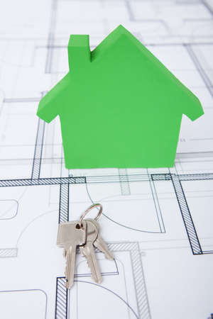 protection plan: Closeup of green house and keys on blueprint Stock Photo