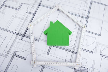 house sketch: Closeup of house in folding ruler on blueprint Stock Photo