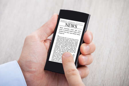 Closeup of businessmans hands surfing news on smartphone at desk photo