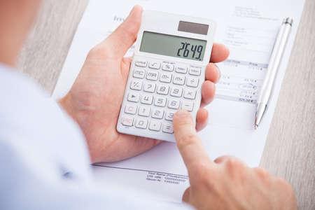 auditor�a: Recorta la imagen de hombre de negocios c�lculo de la factura en el escritorio