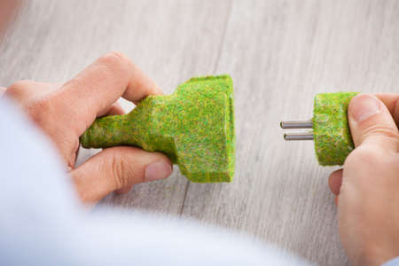 plug in: Cropped image of businessman holding grass covered electric plug and socket at desk in office