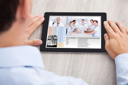 Cropped image of businessman video conferencing with medical team on digital tablet at desk in office photo