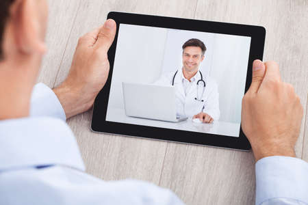 cropped image: Cropped image of businessman video conferencing with doctor on digital tablet at desk in office