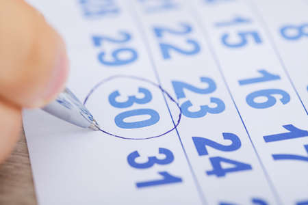 Cropped image of businessman marking date on calendar at desk photo