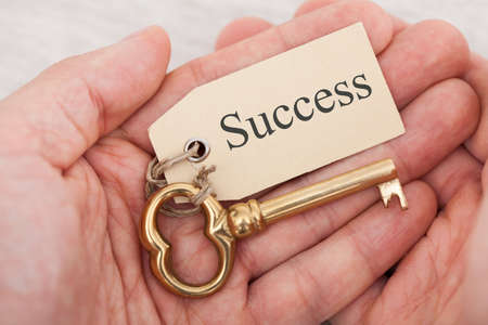 key words: Closeup of man holding golden key with success tag Stock Photo