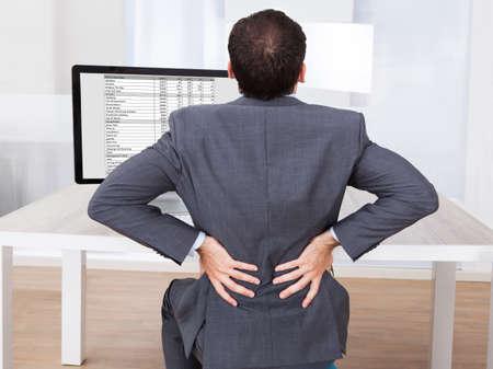 dolor de espalda: Vista trasera del hombre de negocios que sufren de dolor de espalda mientras estaba sentado en el escritorio de la computadora en la oficina