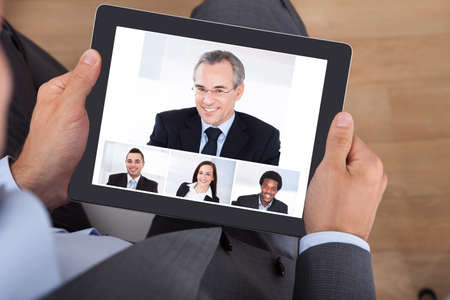 conferencing: High angle view of businessman video conferencing with coworkers on digital tablet in office Stock Photo