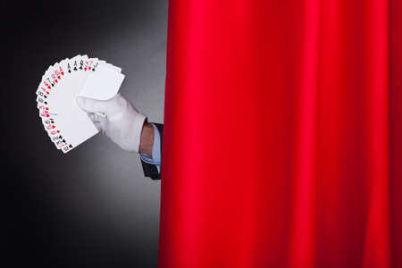 fanned: Cropped image of magician holding fanned cards behind stage curtain