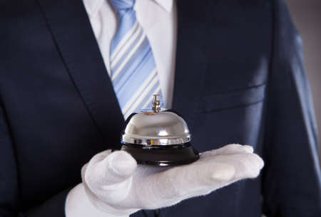 bellman: Midsection of bellman holding bell against black background