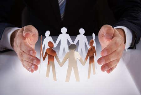 manos unidas: Sección media de manos del empresario de protección de equipo de personas de papel sobre el escritorio Foto de archivo
