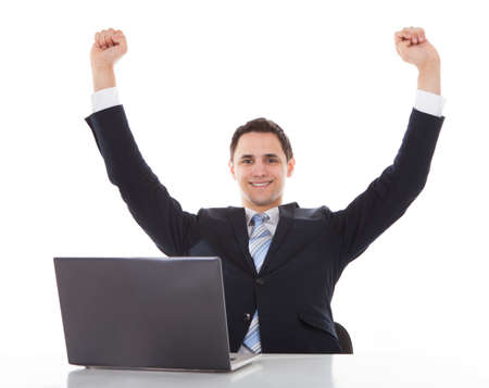 Portrait of smiling businessman celebrating success at desk against white background photo