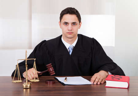 Portrait of confident male judge sitting at table in courtroom photo