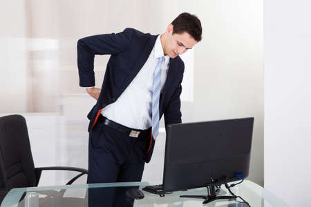 Young businessman suffering from backache in office photo