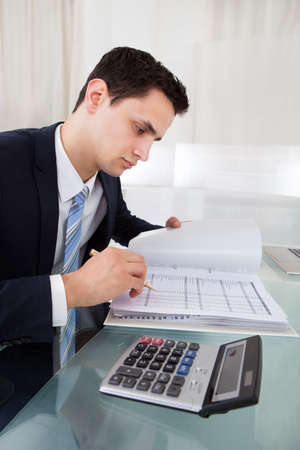 cropped image: Cropped image of businessman calculating expense at desk in office